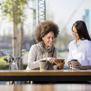 two women sitting outside drinking coffee and chatting