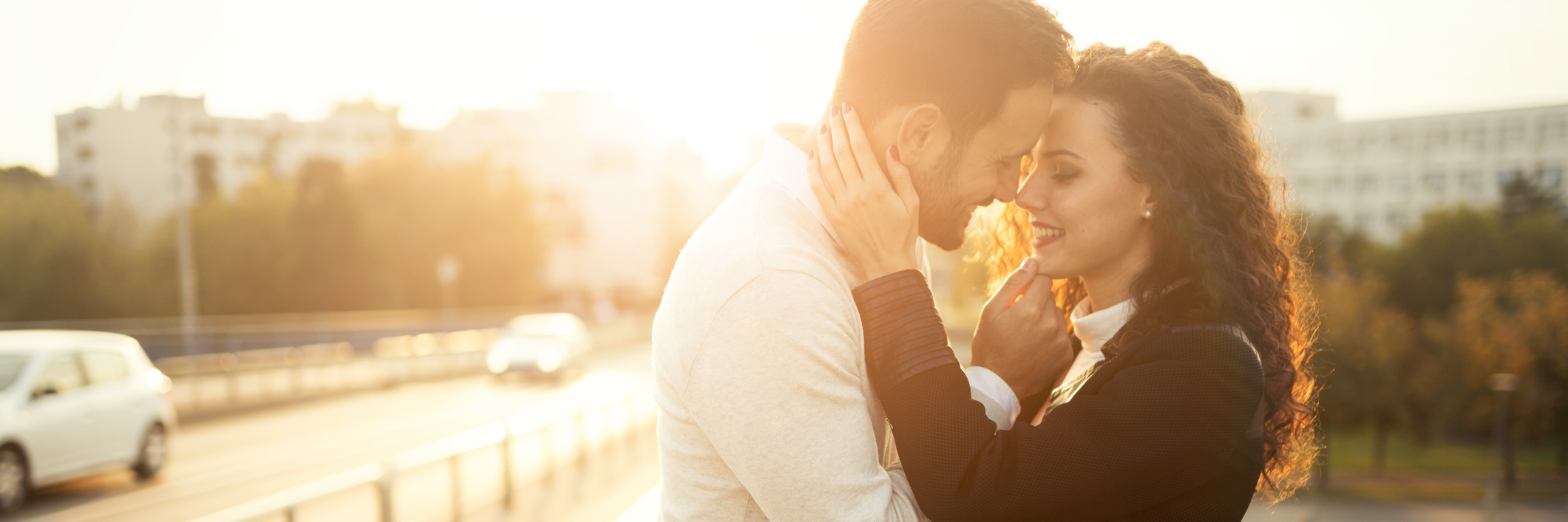 man and woman smiling at each other outdoors at sunset