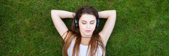 Woman in the grass wearing headphones.