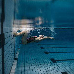 woman swimming laps and doing a flip turn in a pool