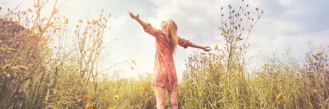 Woman standing in field with outstretched arms, blue sky above her