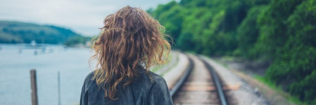 A young woman is walking on the railroad tracks