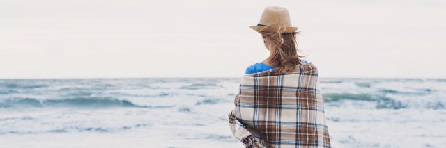 woman standing alone on the beach wrapped in a blanket