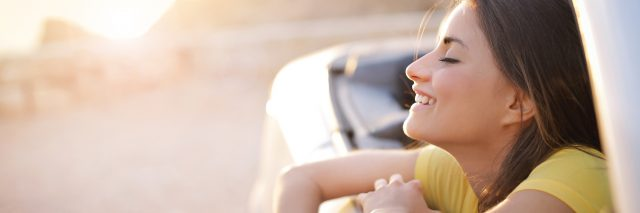 woman leaning out car window smiling and enjoy the air