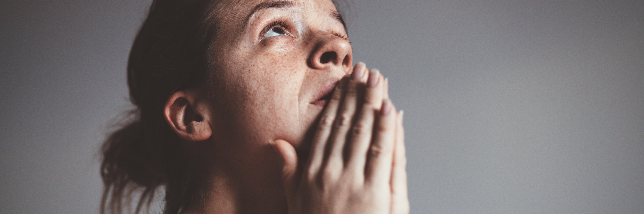 upset woman with tears in eyes and praying against gray background