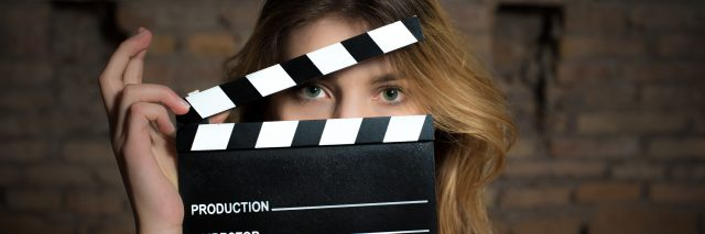 woman holding up a movie clapper in front of her face