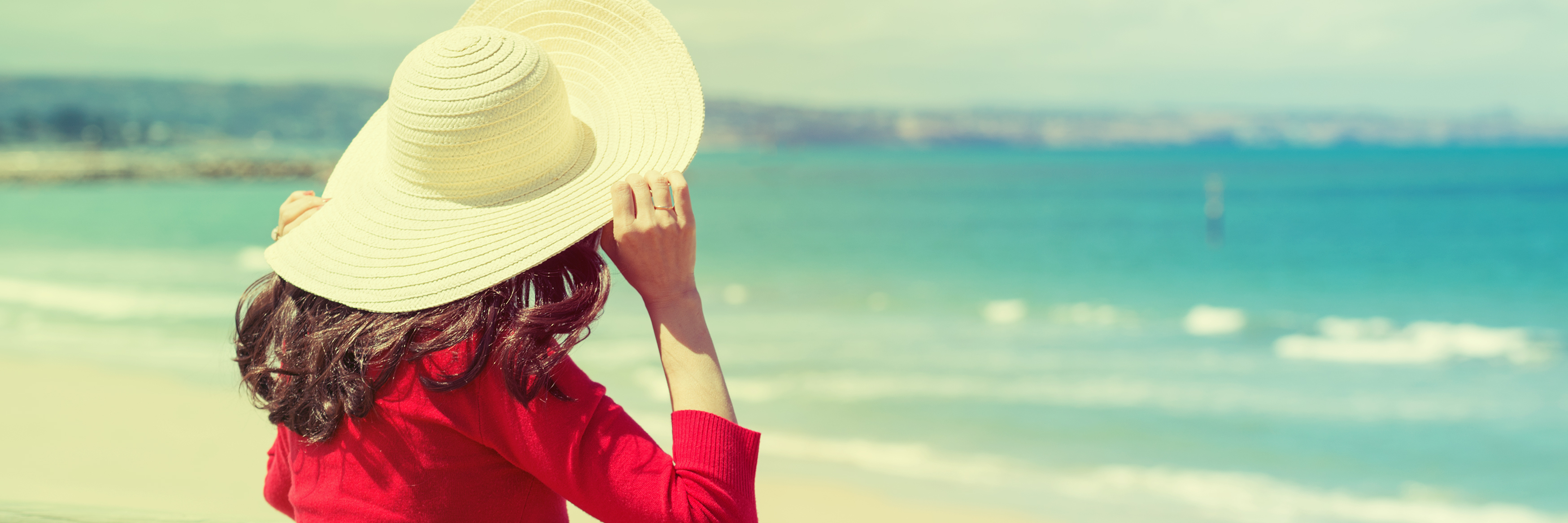 woman wearing hat looking at ocean