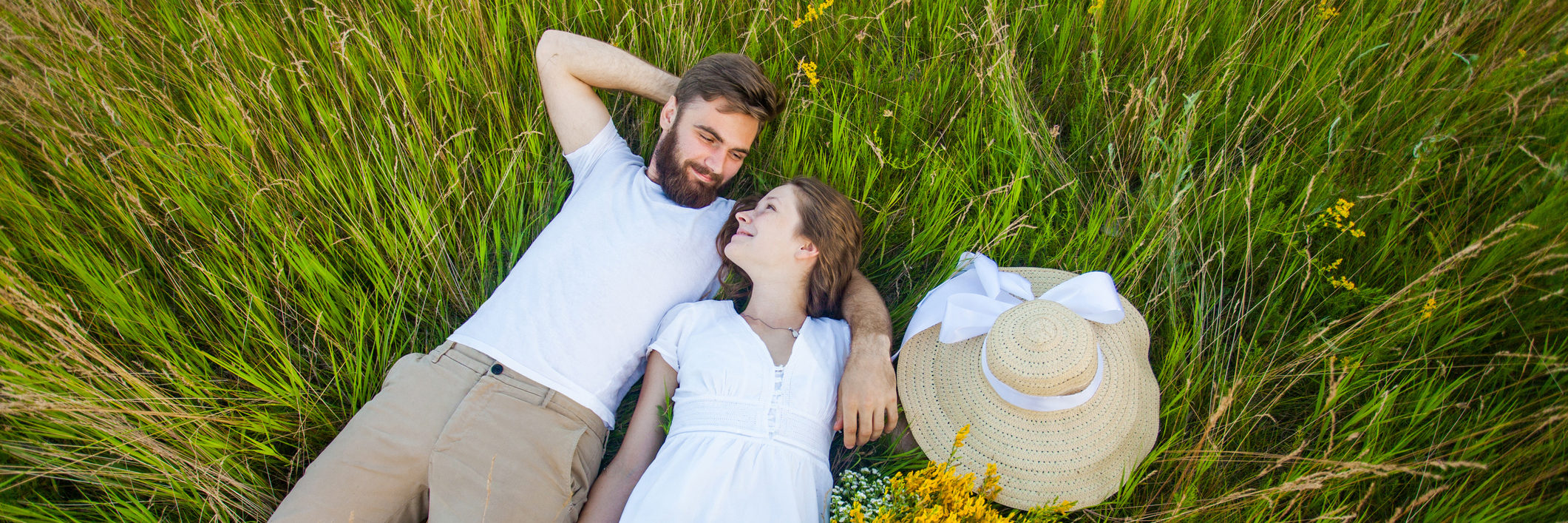A young couple lays in the grass together.