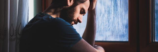 young man sitting at window with head on hand depression