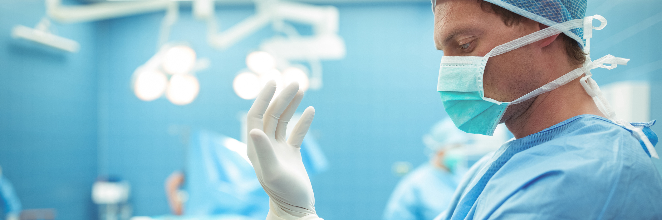 doctor putting on surgical gloves before a procedure