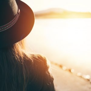 woman wearing a hat and looking at the sunset over a lake