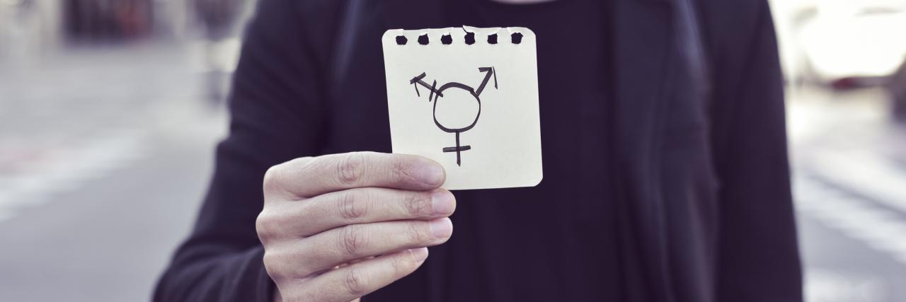 man in blazer holding transgender symbol on notepad