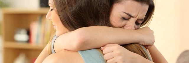 young woman hugging upset friend crying on shoulder support