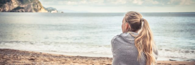 Pensive woman sitting on beach hugging her knees and looking into the distance with hope.