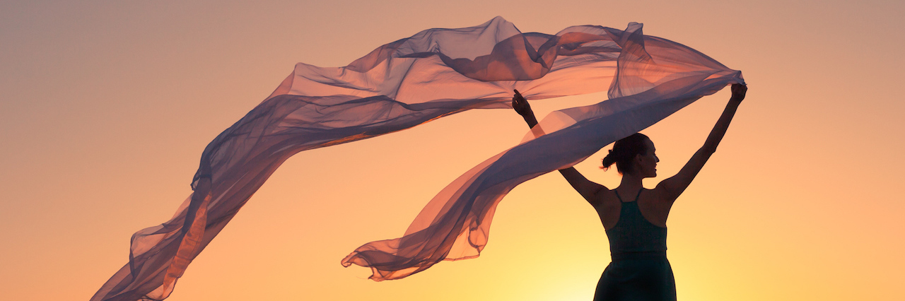 A woman holding a silk cloth in the wind