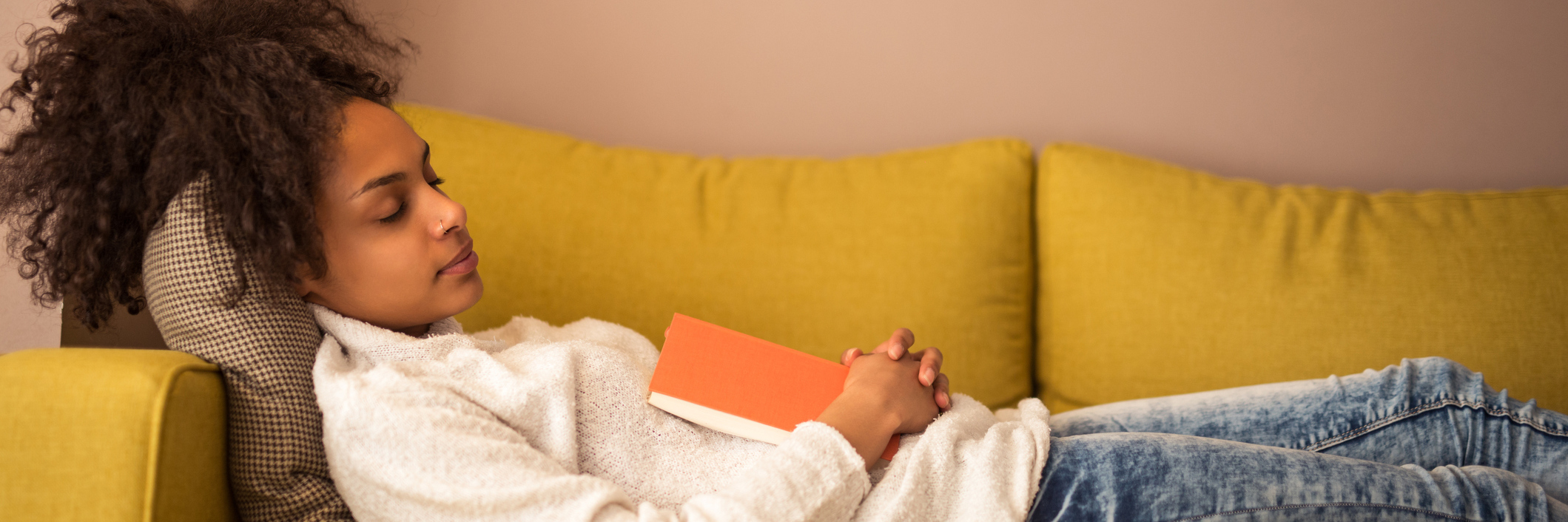 An young woman falling asleep on the couch with a book in hand.