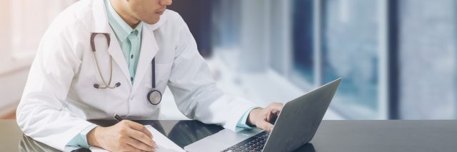 doctor looking at laptop and writing on a notepad