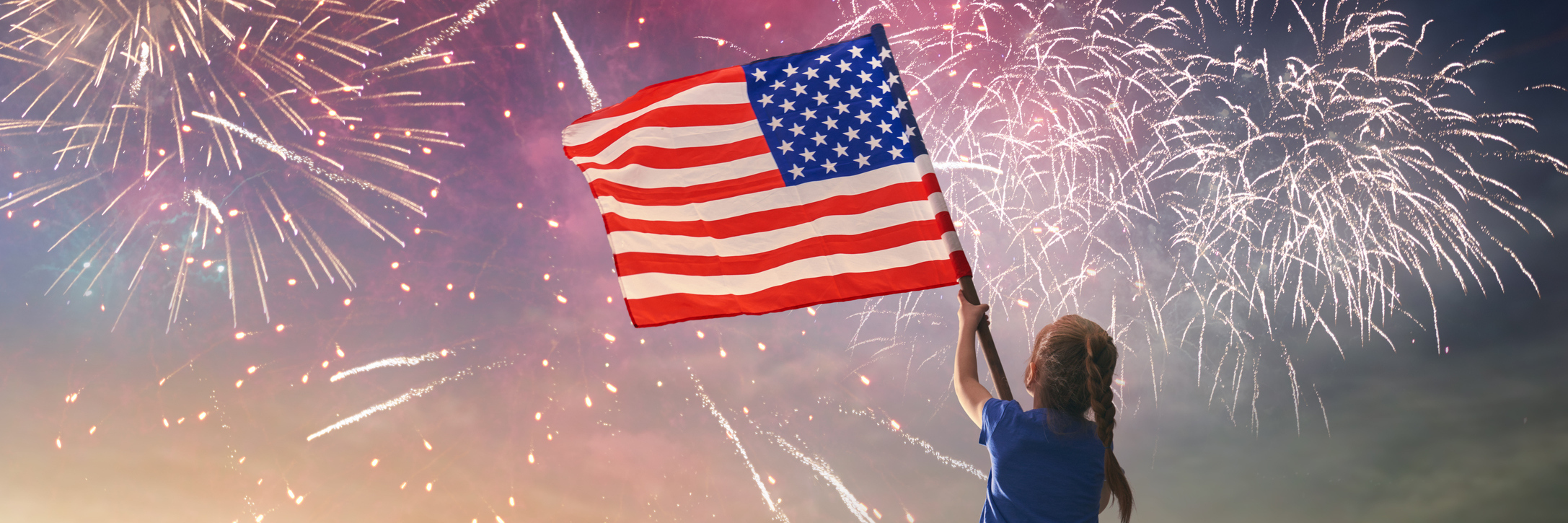 young girl waving an american flag in the sky with fireworks