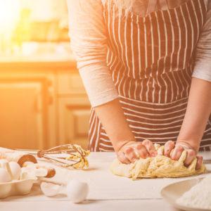 Woman kneading dough on kitchen table.