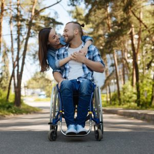 Happy couple, the man uses a wheelchair.