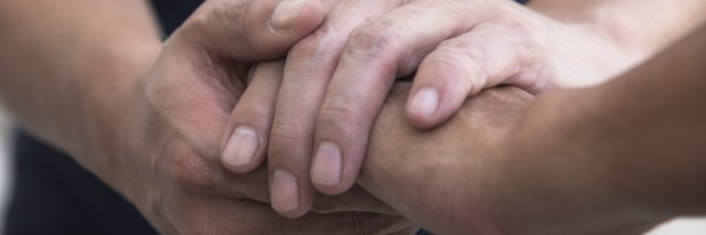 Man holding another man's hand in sympathetic, consoling gesture