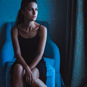 lonely woman sitting in blue room in chair by window