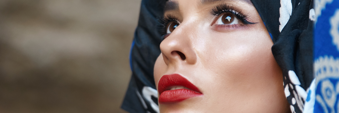 Beautiful woman with a bandana on her head, looking toward sky.