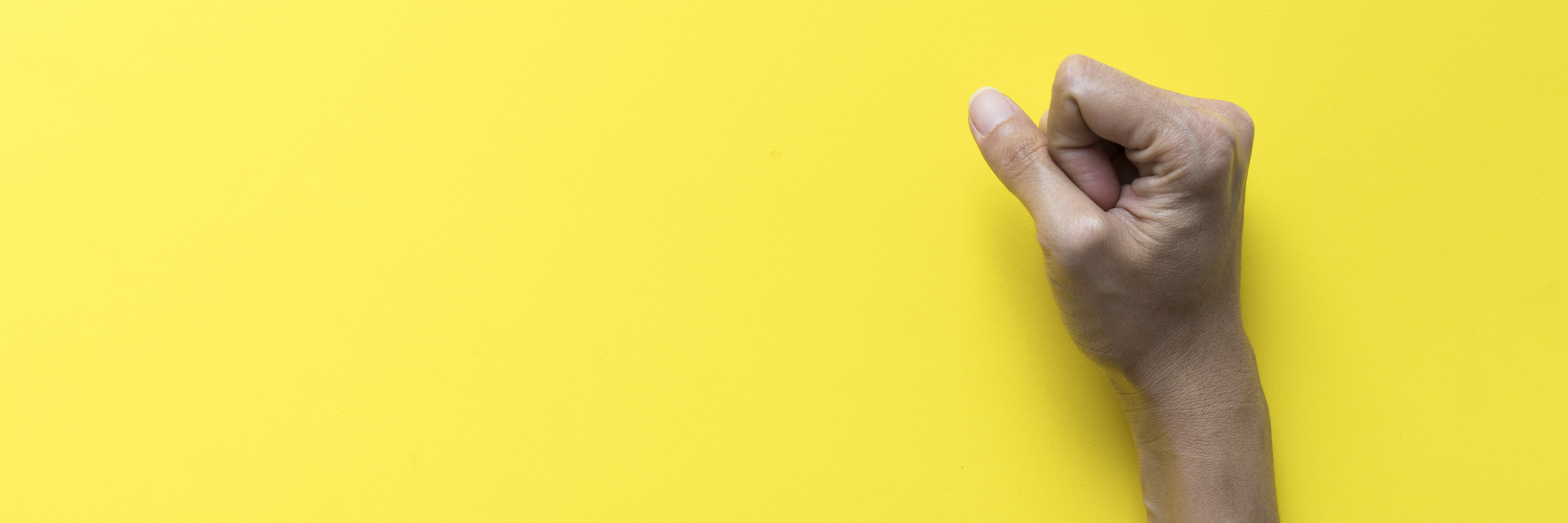 A females fist clinched on a yellow background.