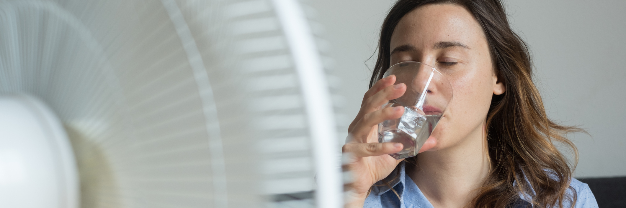 woman drinking water and sitting in front of a fan
