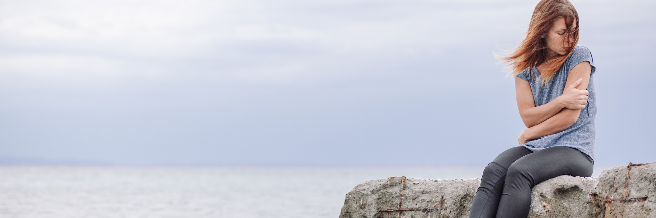 woman alone at seaside sitting on rocks looking depressed arms folded