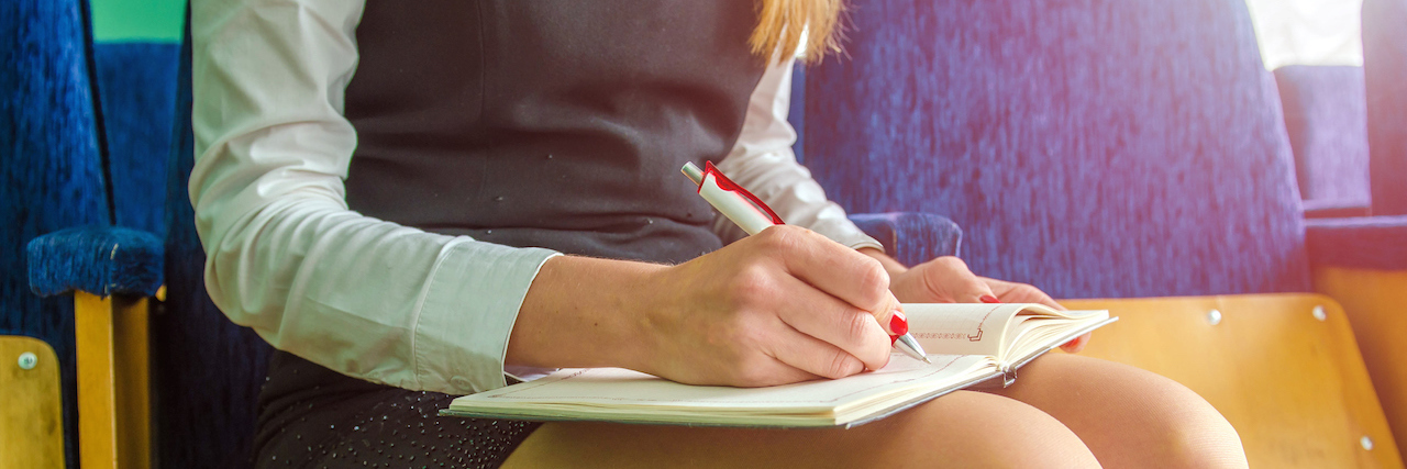 woman writing in her notebook