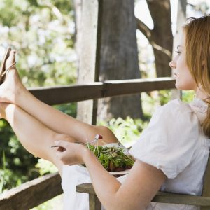 Woman relaxing outdoors in sunshine with feet up on wooden railing