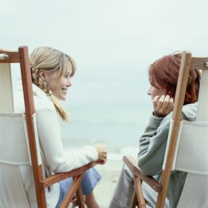 two women sitting in chairs on the beach and talking