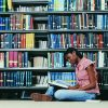 Female University student sitting in library reading a book.