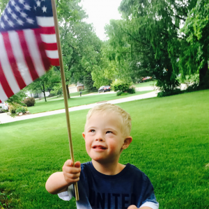 Troy, a little boy with Down syndrome holding an American flag.