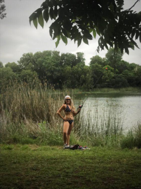 Photo of a woman by a lake wearing a bikini