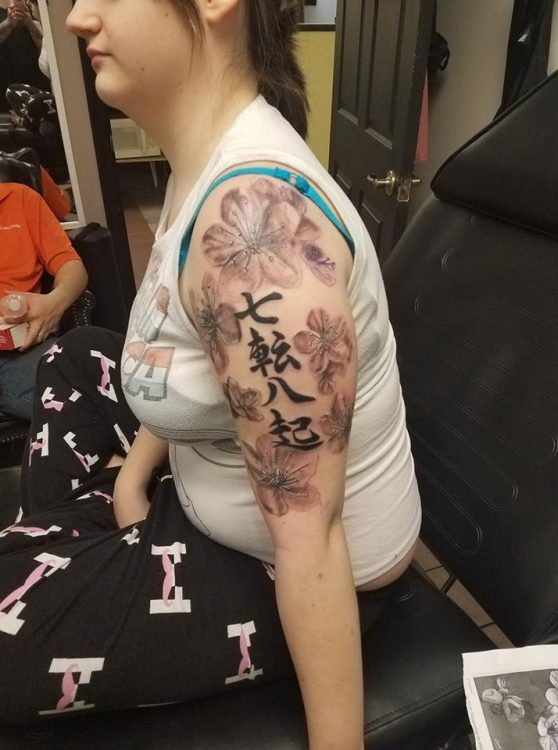 chinese symbols and flowers tattoo on arm