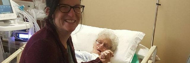 woman holding her grandmother's hand in the hospital