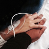 woman's hand with an IV holding a man's hand
