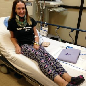 The writer sitting on a hospital bed while wearing a neck brace.
