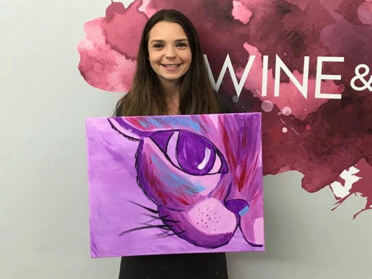woman smiling and holding a painting she made