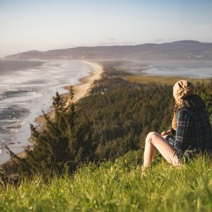 woman sitting outdoors in nature overlooking coastline and forest