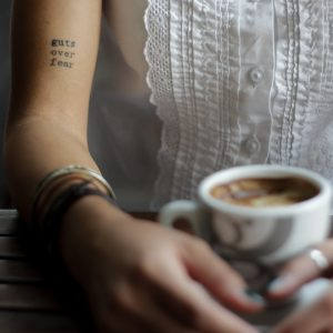 woman sitting at a table holding a coffee with a tattoo on her arm that says 'guts over fear'