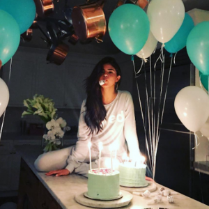 selena gomez instagram on birthday, sitting on table with cake surrounded by balloons