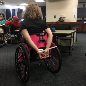 Disability rights activist Stephanie Woodward sits in her pink manual wheelchair with her hands cuffed behind her back.