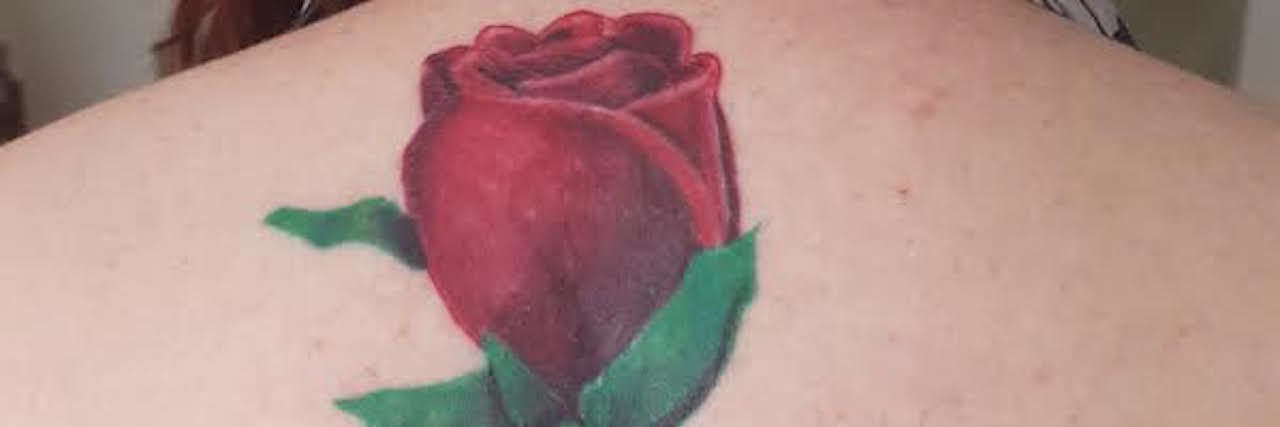 tattoo of a rose on a woman's spine