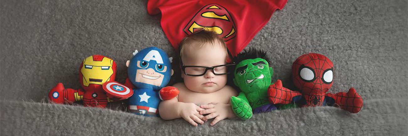 Bbay boy with Down syndrome wearing glasses, sleeping, superman cape above him while i the middle of stuffed superheroes