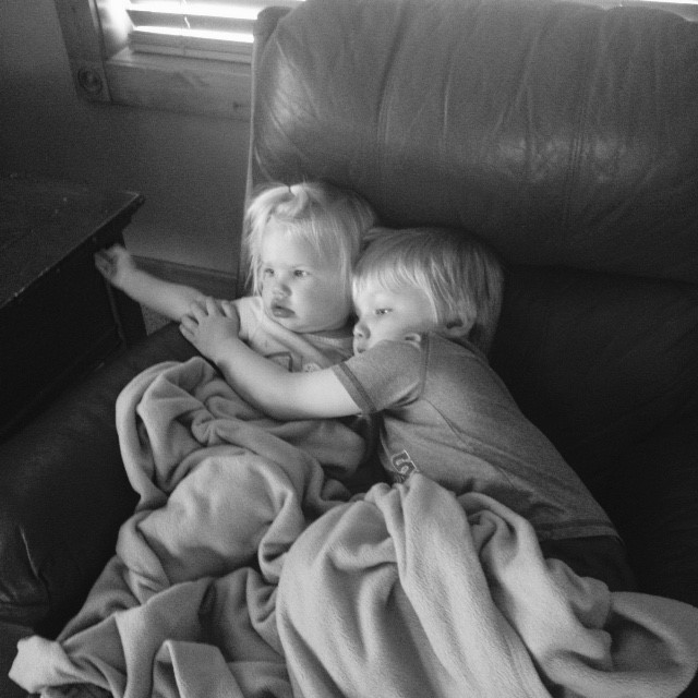 toddler boy and girl sitting on a couch under blankets hugging