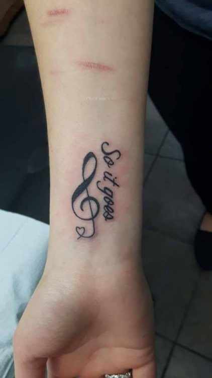 treble clef and words tattooed on wrist