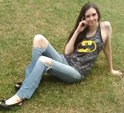 Woman sits on grass, wearing a Batman shirt.